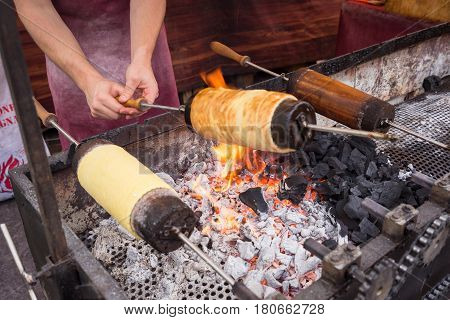 Kurtos kalacs or Chimney Cakes roll spinning over hot coals at a market standthe typical sweet of BudapestHungary