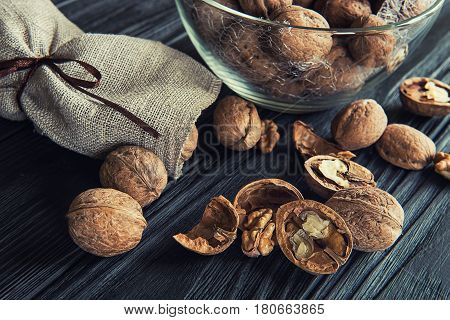 Some walnuts on a black wooden table background.