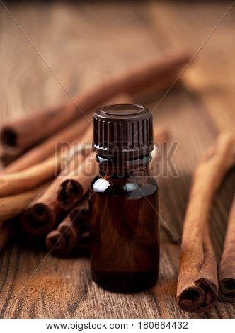 Glass bottle with essential oil of cinnamon cinnamon sticks on a wooden background