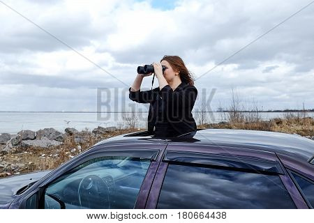 young beautiful girl looking through binoculars from a car