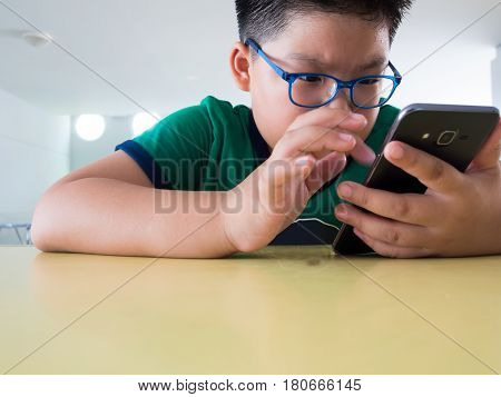 Close up serious asian boy playing on smartphone