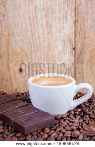 warm cup of coffee and chocolate on wooden background