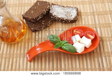 Fresh cherry tomatoes, bread, chees, basilic and chili pepper on red plate