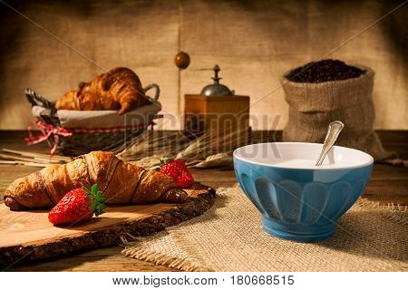 Continental breakfast with croissant and milk over an old wooden table