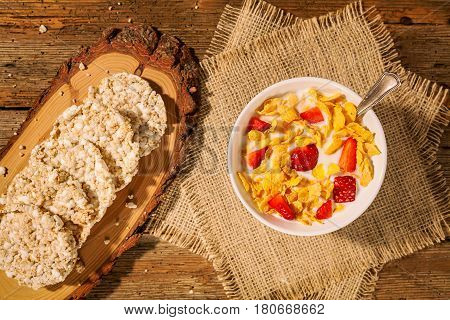 Continental breakfast with cornflakes strawberries rice crackers and a cup of milk seen from above