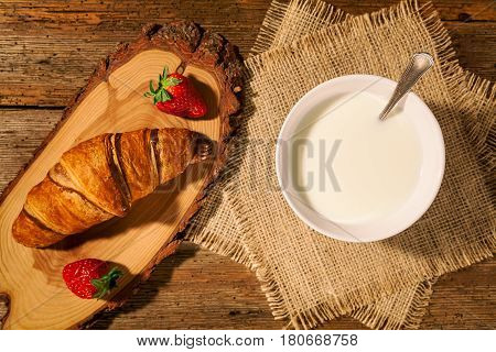 Continental breakfast with croissant strawberries and a cup of milk seen from above