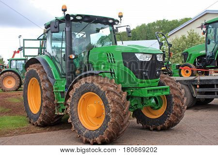 Farm tractors standing ready for transport on a truck