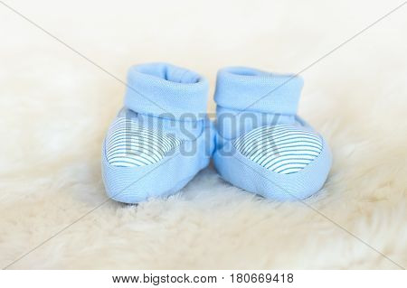 Blue baby newborn booties on white background