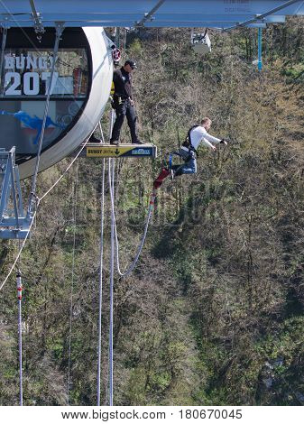 Sochi - April 4 2017: A brave man with a special rubber rope jumping from the world's longest pedestrian bridge in the Akhshtyrsky Gorge April 4 2017 Sochi Russia