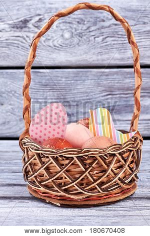 Easter eggs and paper cutouts. Wicker basket on wood surface.