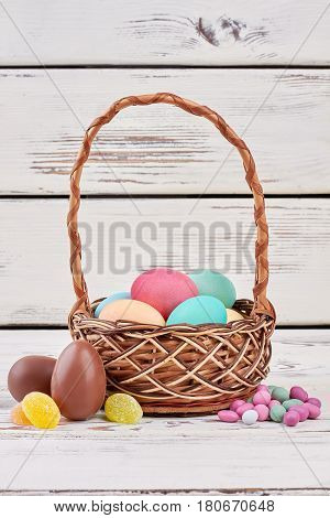 Easter egg basket and candies. Chocolate eggs on wooden surface. Easter goodies for kids.