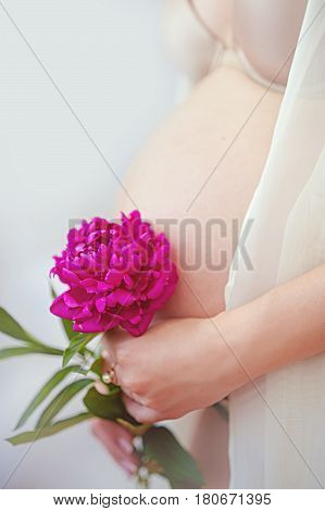 pregnant woman with pink flower. Healthy maternity concept
