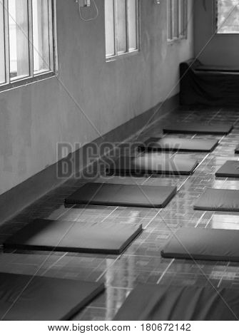BLACK AND WHITE PHOTO OF ARRANGED MEDITATION CUSHIONS IN MEDITATION CENTER