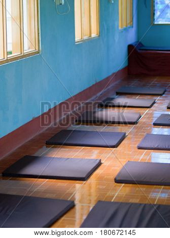 COLOR PHOTO OF ARRANGED MEDITATION CUSHIONS IN MEDITATION CENTER