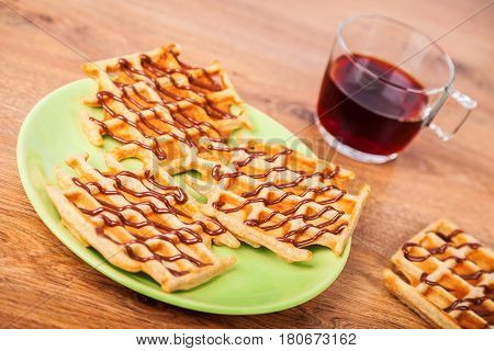 Plate with homemade Belgian waffles and a cup of black tea closeup