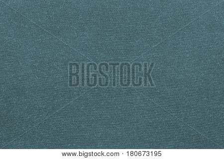 background and texture of knitted or woolen fabric of monotonous dark turquoise color