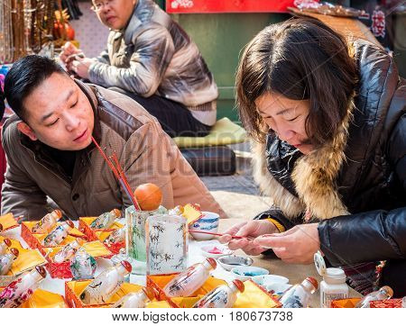 Tianjin, China - Nov 1, 2016: Lady painting Qing Dynasty style snuff bottle while a man looks on. Along Tianjin Ancient Cultural Street. Morning scene to what is a very popular tourist area.