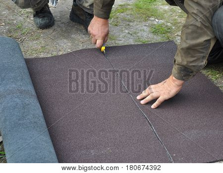 Roofer cutting roll roofing felt or bitumen during waterproofing works. Roofing repair.Woker Install and Repair Asphalt Shingles fot the Rooftop Outdoor.