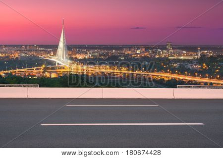 Side view on highway and the city in background shiny new bridge as well as modern access roads at idyllic purple sunset.