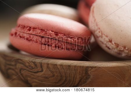 closeup shot of pastel colored macarons with strawberry, rose and caramel flavour in wood bowl, macro photo