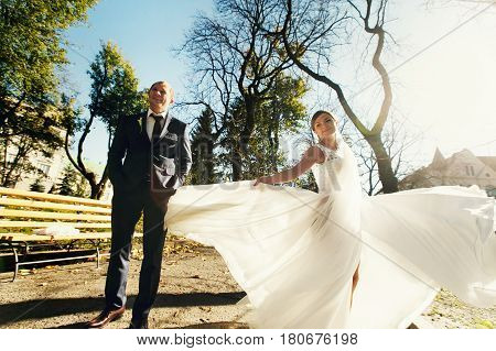 Groom Stands Straight Behind A Whirling Bride