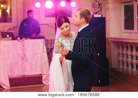 Bride Looks Down Dancing With A Groom In Pink Lights