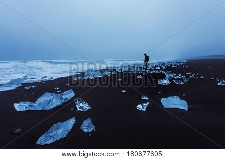 A photographer stands silhouetted and alone on Jokulsarlon's ice beach. Jokulsarlon is located along the southern coast of Iceland.