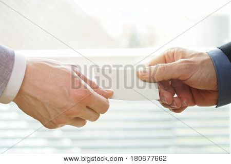 Businesspeople exchanging Visiting Card In Office with sunshine. You can use the blank visiting card as copyspace.