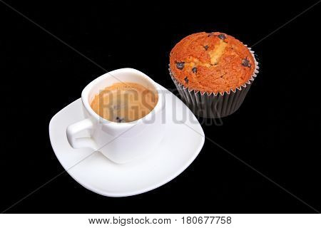 Fresh homemade muffin, cake and white cup of Cappuccino on dark background