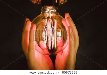 Edison type bulbs in Beautiful girl hands close-up