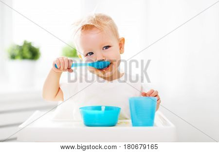 Happy baby eating himself with a spoon