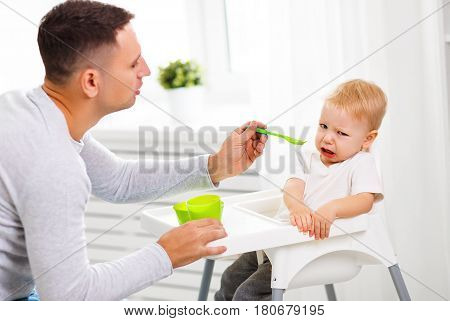 Father feeds the cry baby son with a spoon
