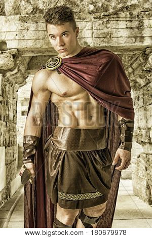 Young handsome muscular man posing in roman or spartan gladiator costume with shield and sword in stone building