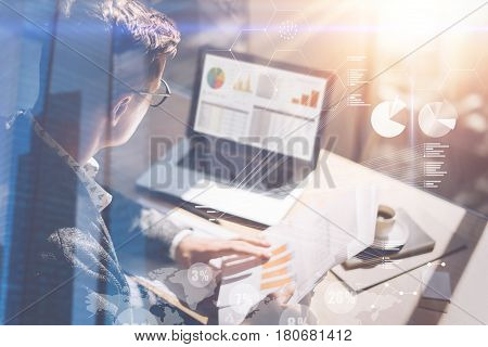 Young businessman analyze stock report on notebook screen.Concept of digital screen, virtual connection icon, diagram, graph interfaces on background.Double exposure