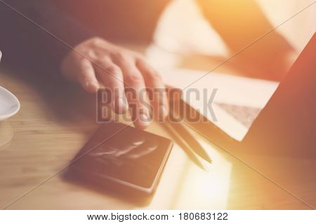 Closeup view of businessman pointing finger on smartphone screen.Elegant coworker working at sunny office on laptop.Blurred background.Sunlight effects.Horizontal