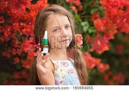 Allergy. Little girl near spring tree in bloom with nasal spray