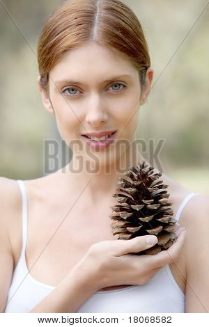 Portrait of beautiful woman holding pine cone poster