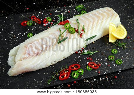 Fresh Raw Cod loin fillet with rosemary, chillies, cracked pepper and lemon on stone board.