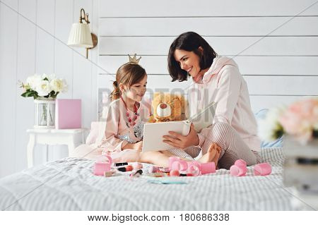 There are mother and her daughter at the girlish bedroom. They are staring at the book and laughing at something