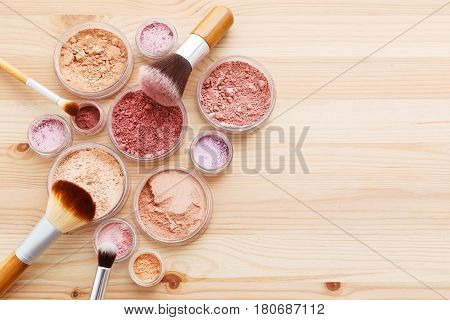 Makeup Powder And Brushes On Wood Background