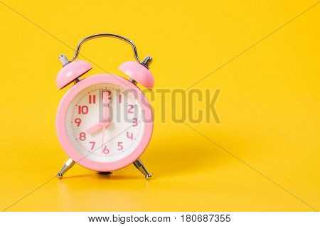 Vintage pink alarm clock on yellow background with copy space.