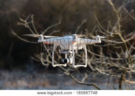 Niedernhausen Germany - February 25 2017: DJI Phantom 3 Standard Quadcopter flying in front of wintry vegetation front view closeup