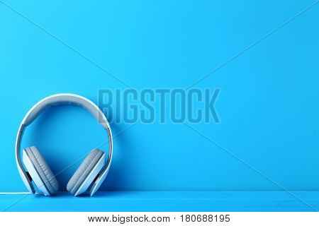 White headphones on the blue background, close up