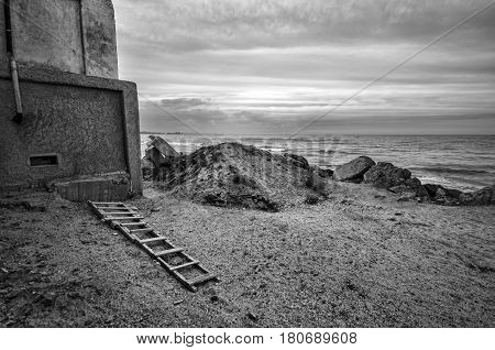 Beautiful Surreal Landscape Of Abandoned House And Ladder On Rocky Seashore At Sunset Time. Cloudy W