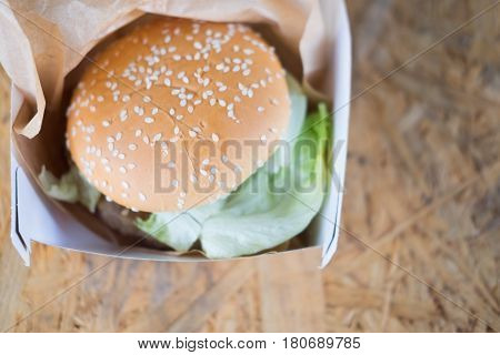 Hamburger and fresh vegetables composition in paper box