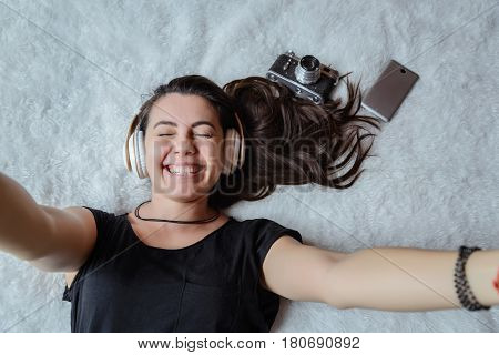 woman taking selfie in bed while listening music