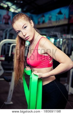Charming young woman workout with rubber bands at fitness gym.Pretty athletic girl with long blonde hair uses green stretch band while exercising in a fitness center.