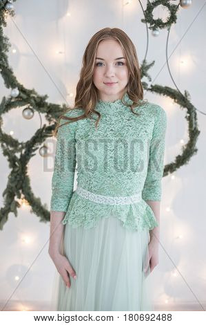 Young beautiful woman with hair of medium length in blue turquoise evening dress in front of a white wall decorated with fairy lights and fir branches poses for the camera.