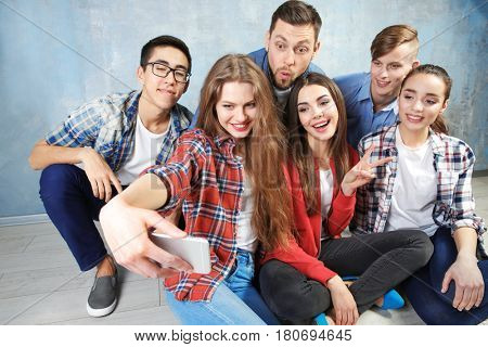 Happy friends taking selfie while sitting on floor indoors