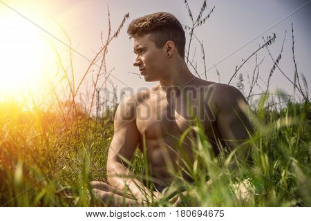 Handsome Muscular Shirtless Young Hunk Man Outdoor in Nature Sitting on Grass. Showing Healthy Muscle Body While Looking away